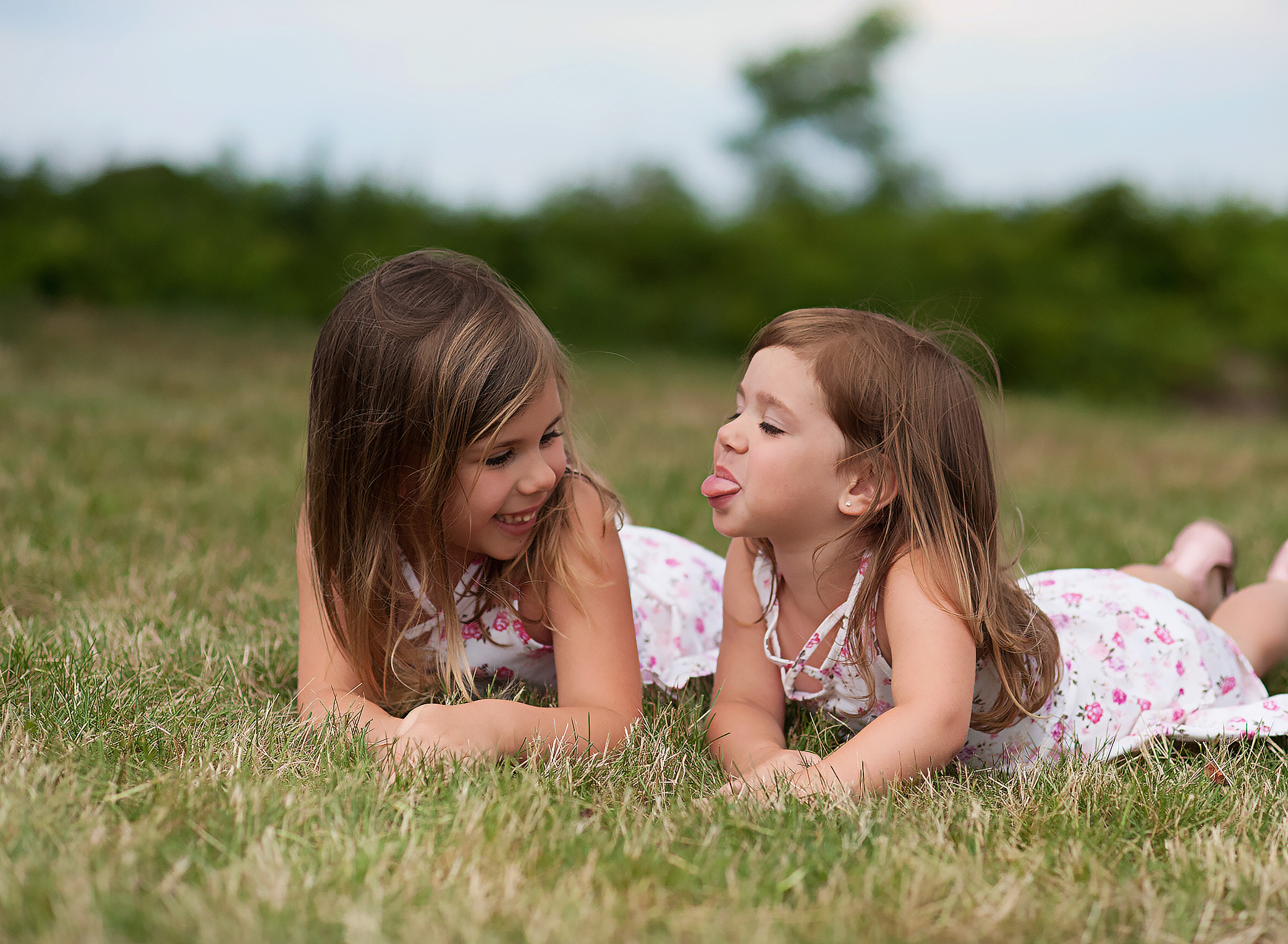 little sister stiking her tongue out at big sister