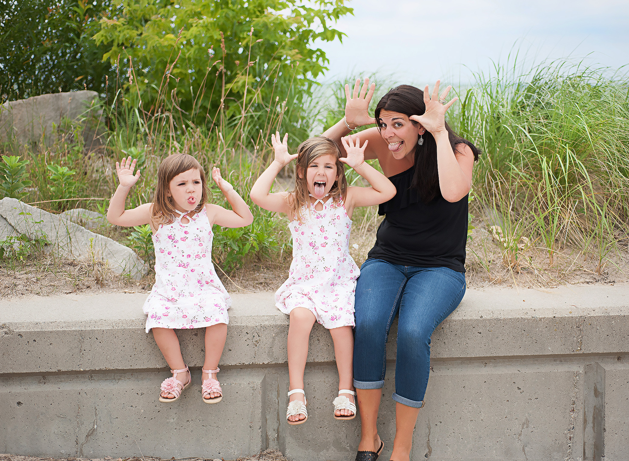 mom and daughters making silly faces at the beach