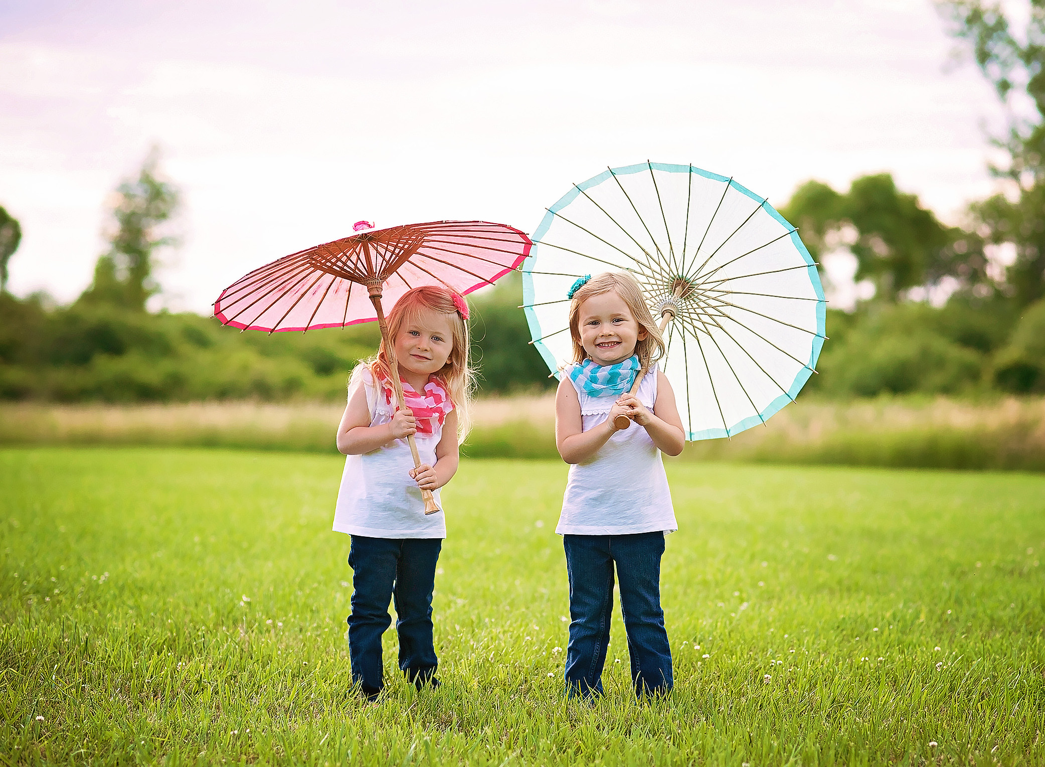 twin girls with paper umbrellas