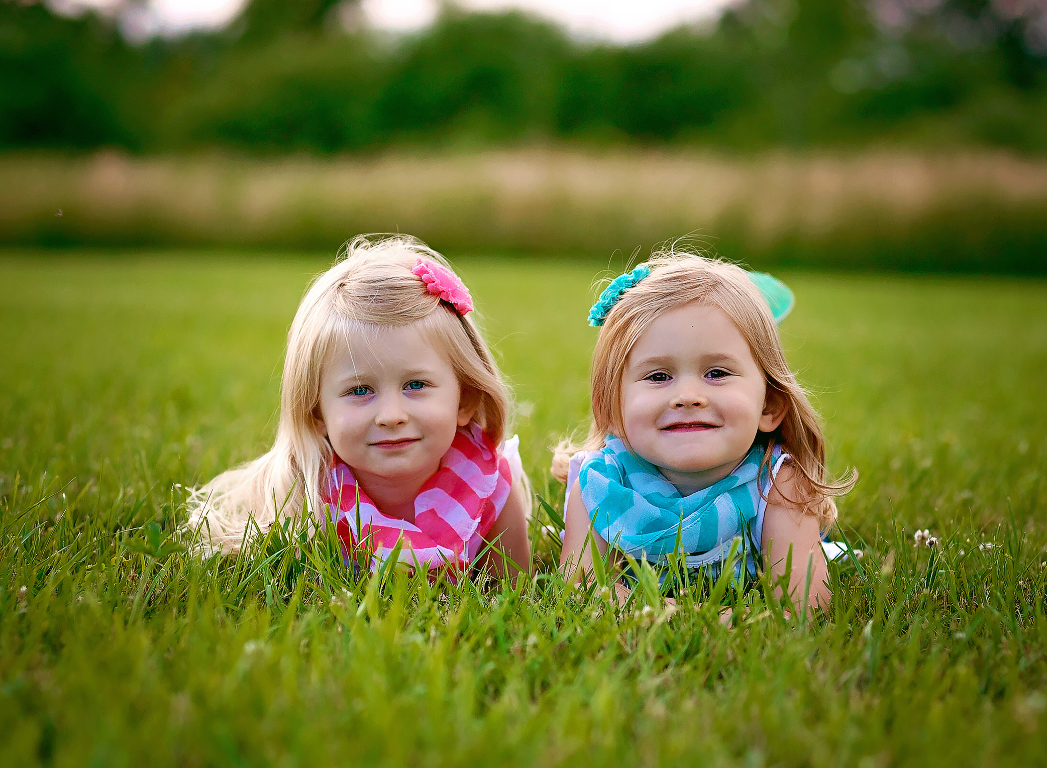 twin girls laying in the grass