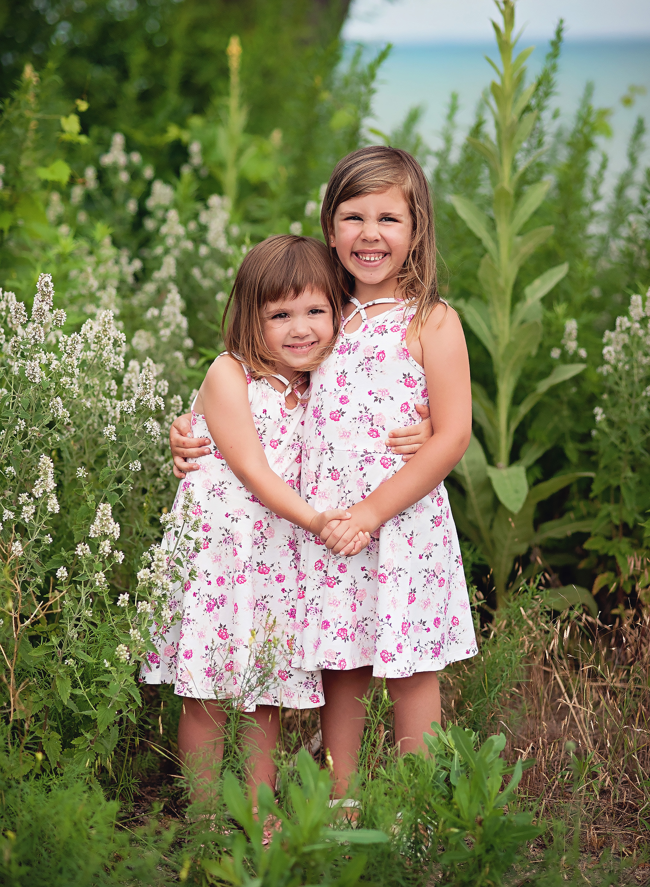 sisters standing and hugging in a field