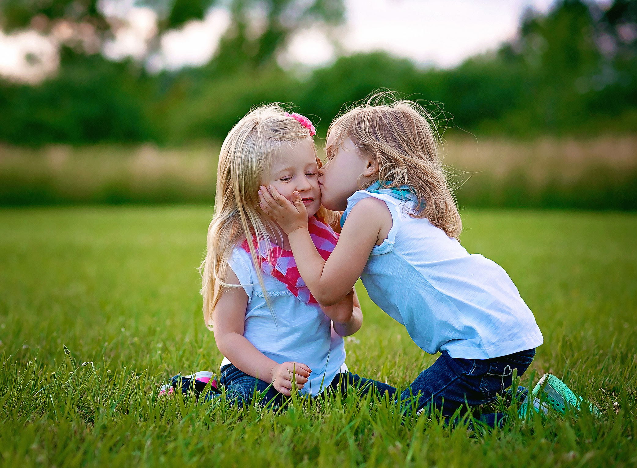 twin girls giving a kiss on the cheek