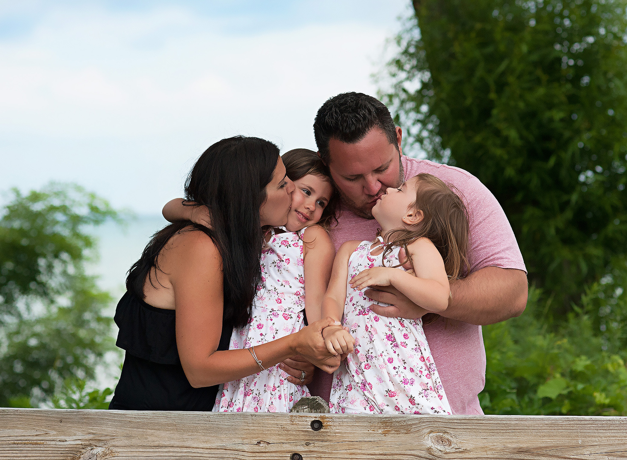 family hugging against a fence