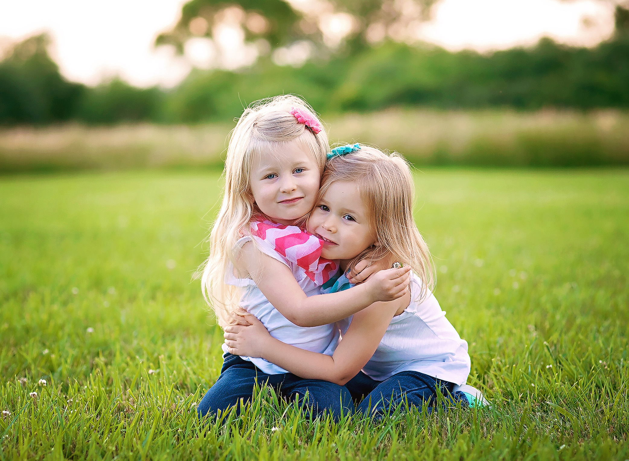 twin girls hugging in the grass