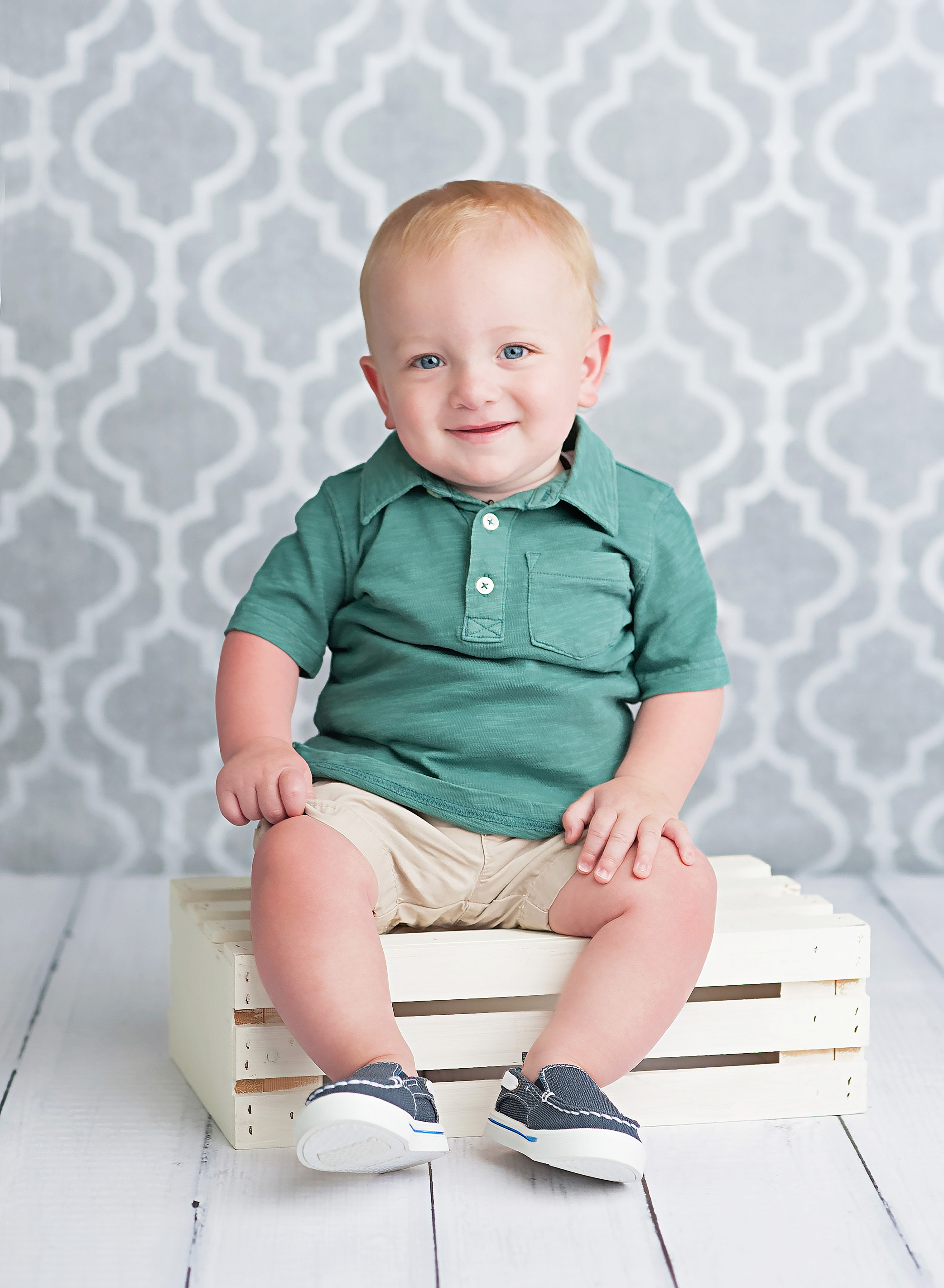 one year olf boy sitting on white crate
