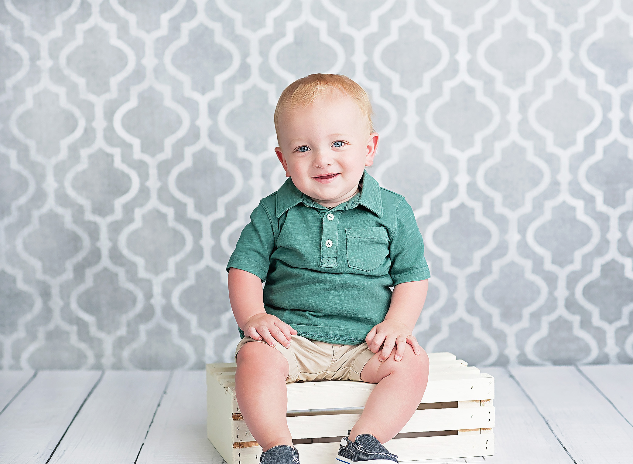 one year old boy siting on white crate