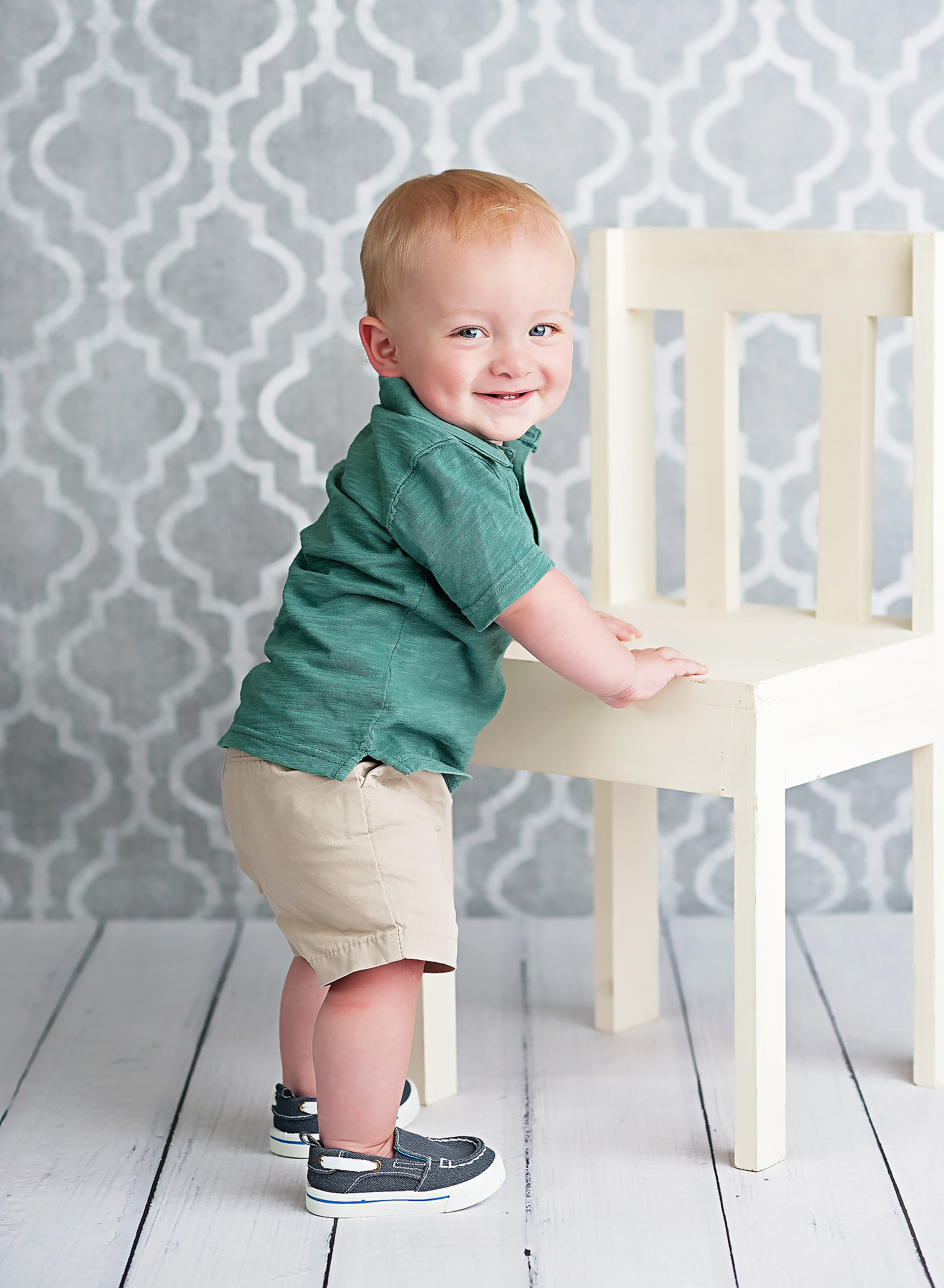 one year olf boy standing by white chair