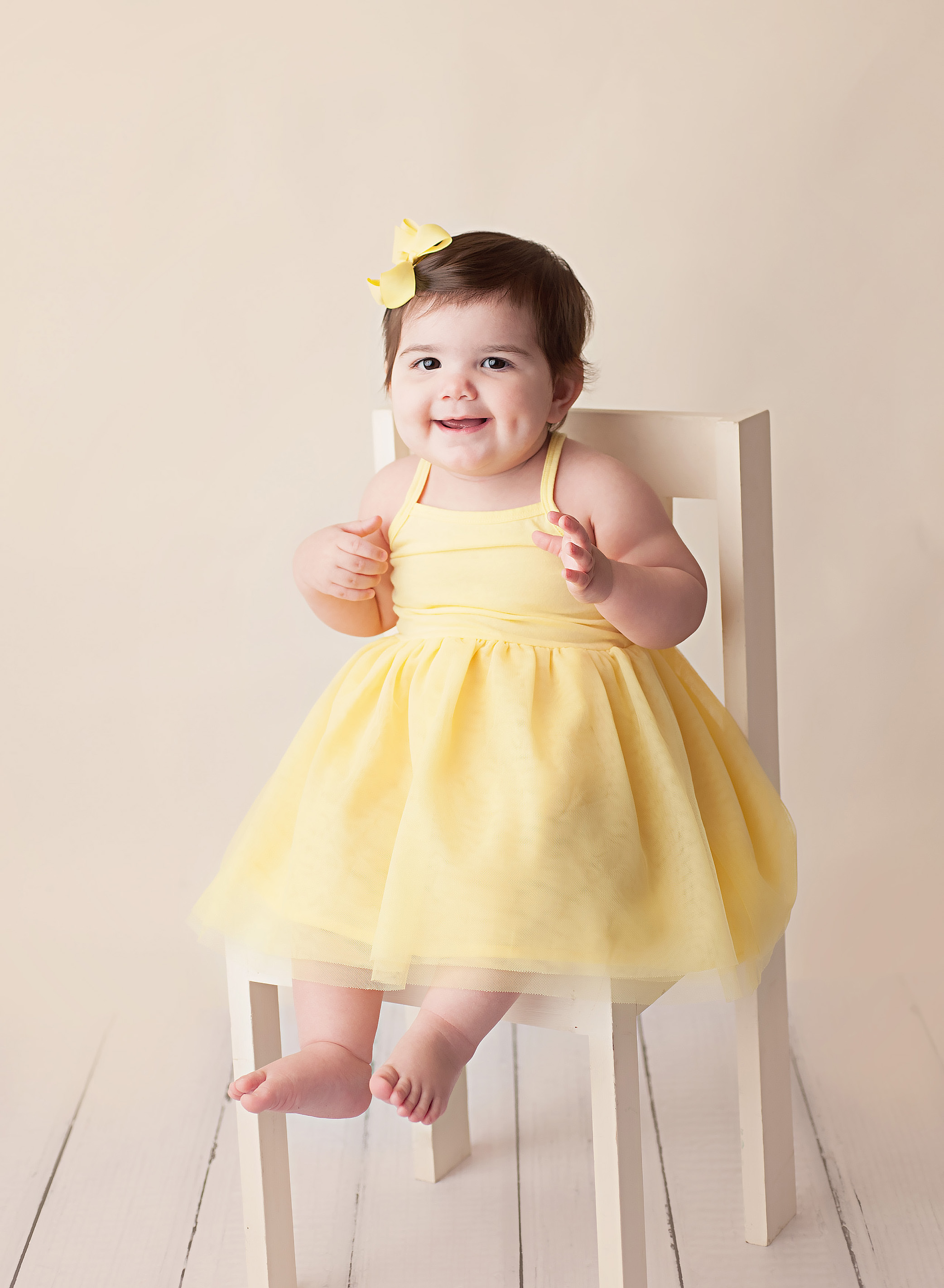 girl in yellow dress on white chair