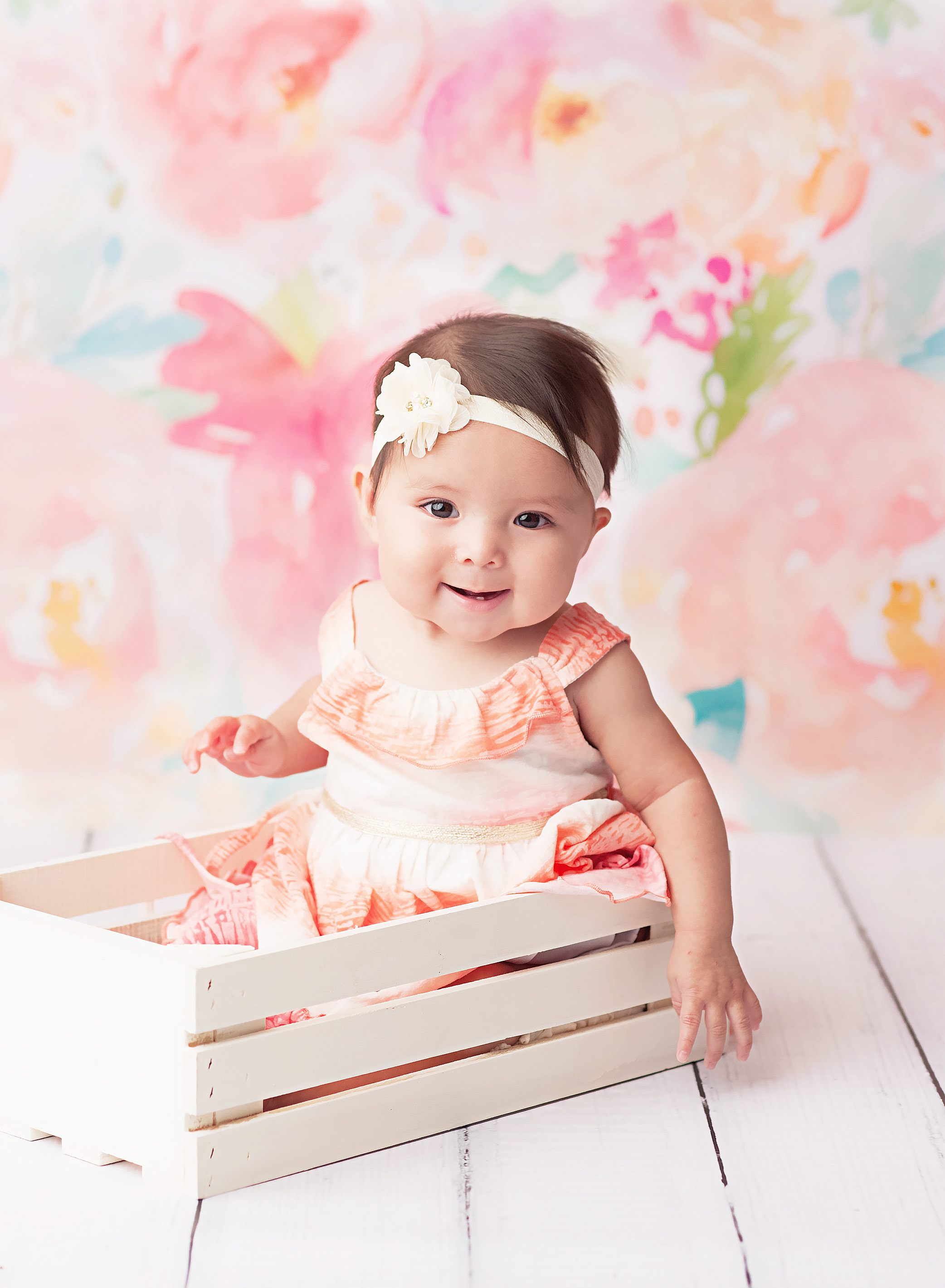 baby girl in white crate against floral backdrop