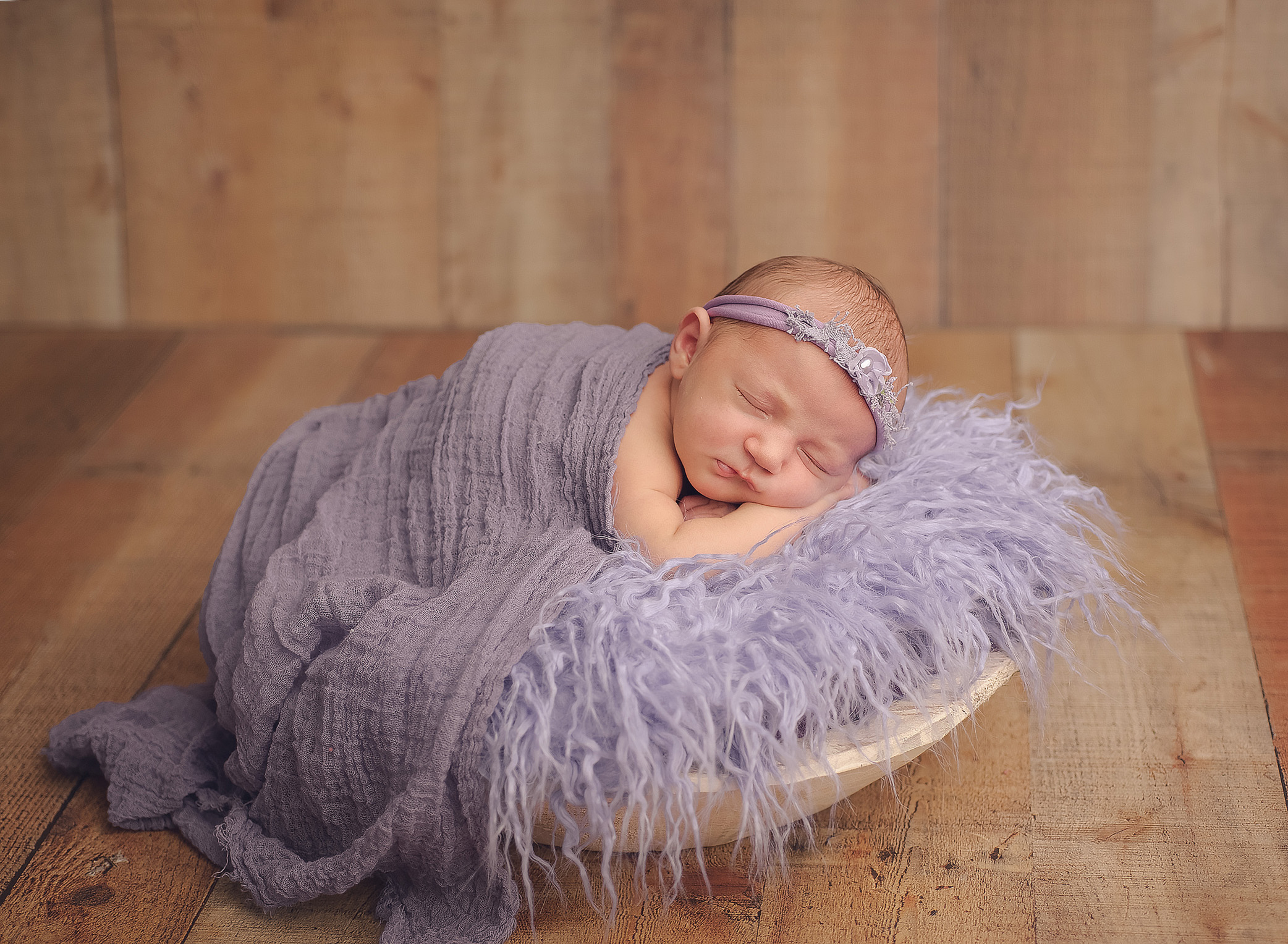 baby laying in purple fur with purple hat