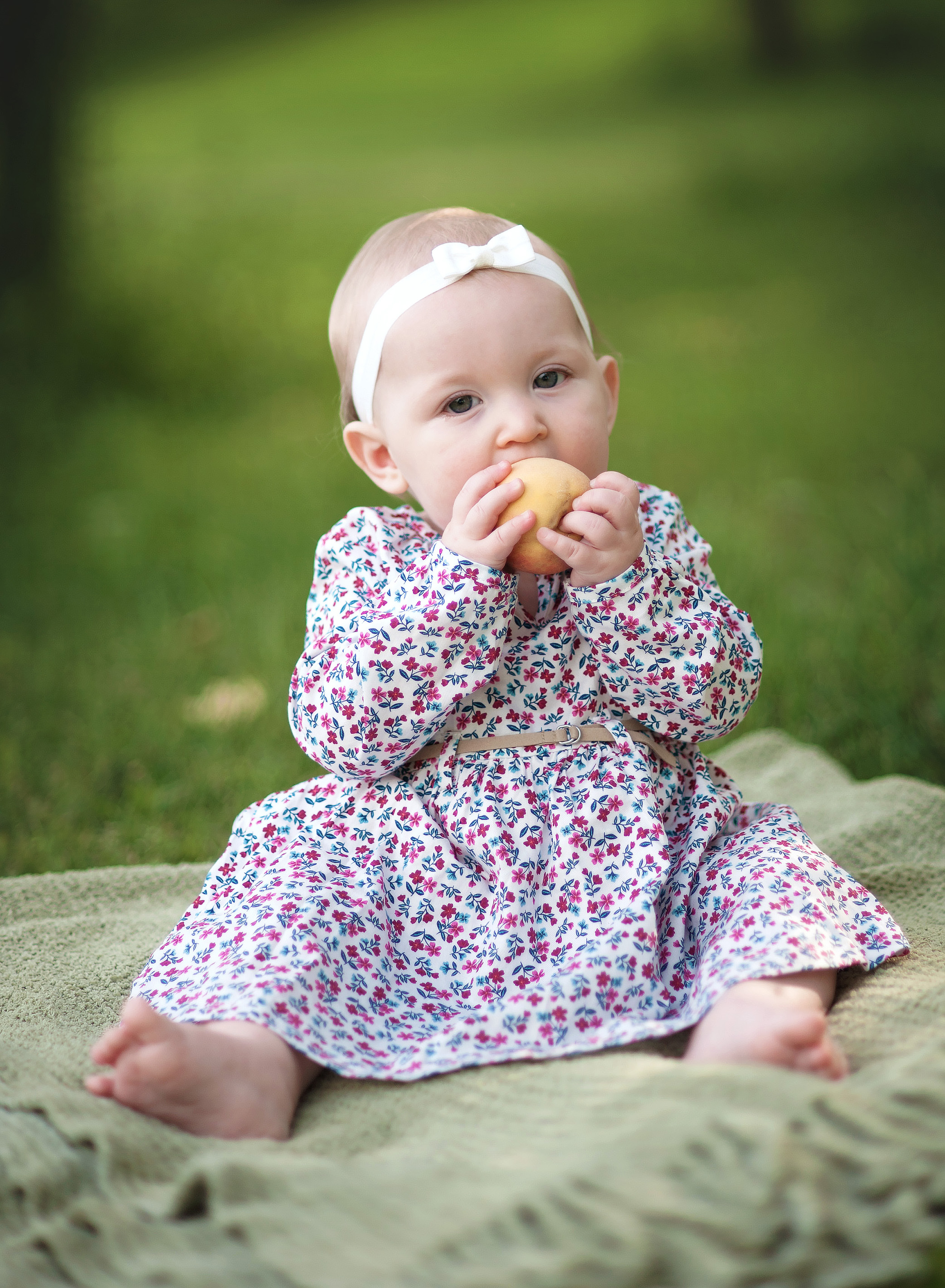 baby eating a peach in a dress