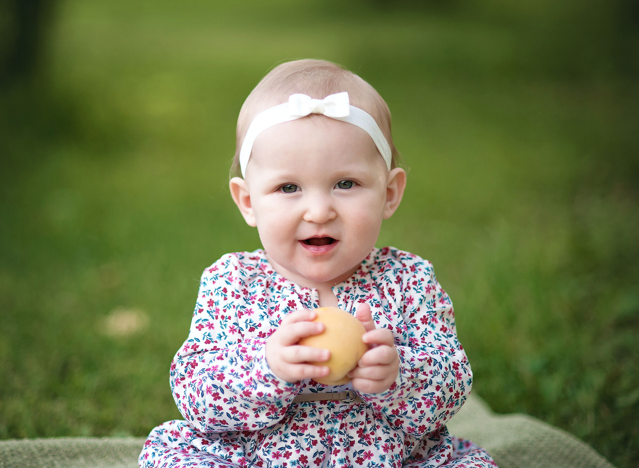 baby eating a peach outside