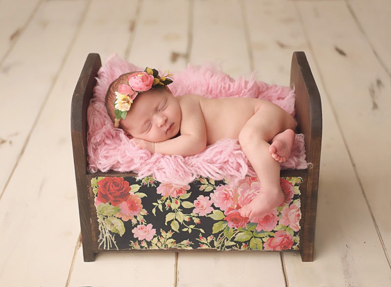 newborn baby in wooden floral bed