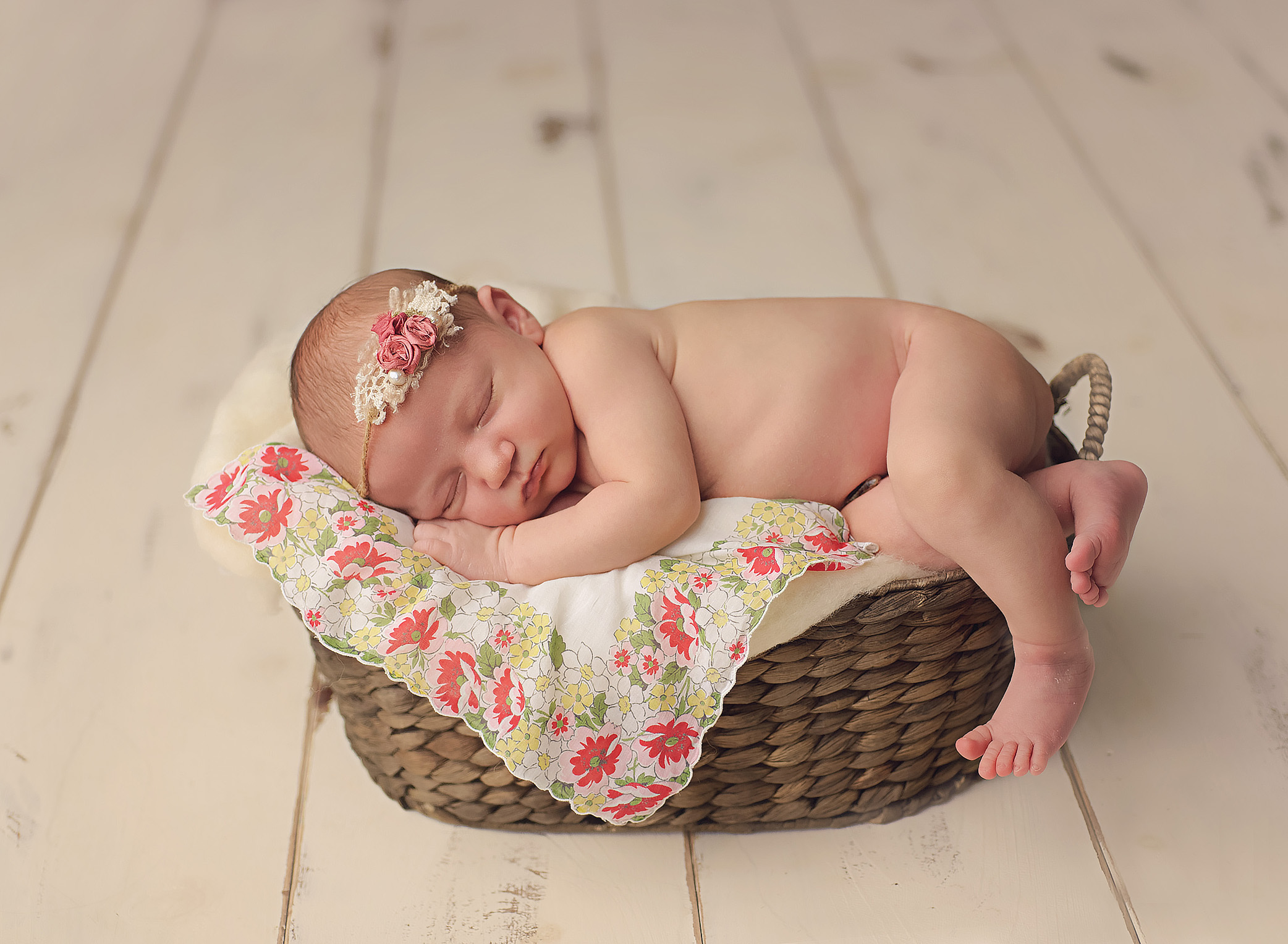 baby in basket with pink headband