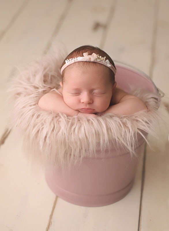 baby in mauve bucet with pink bow headband
