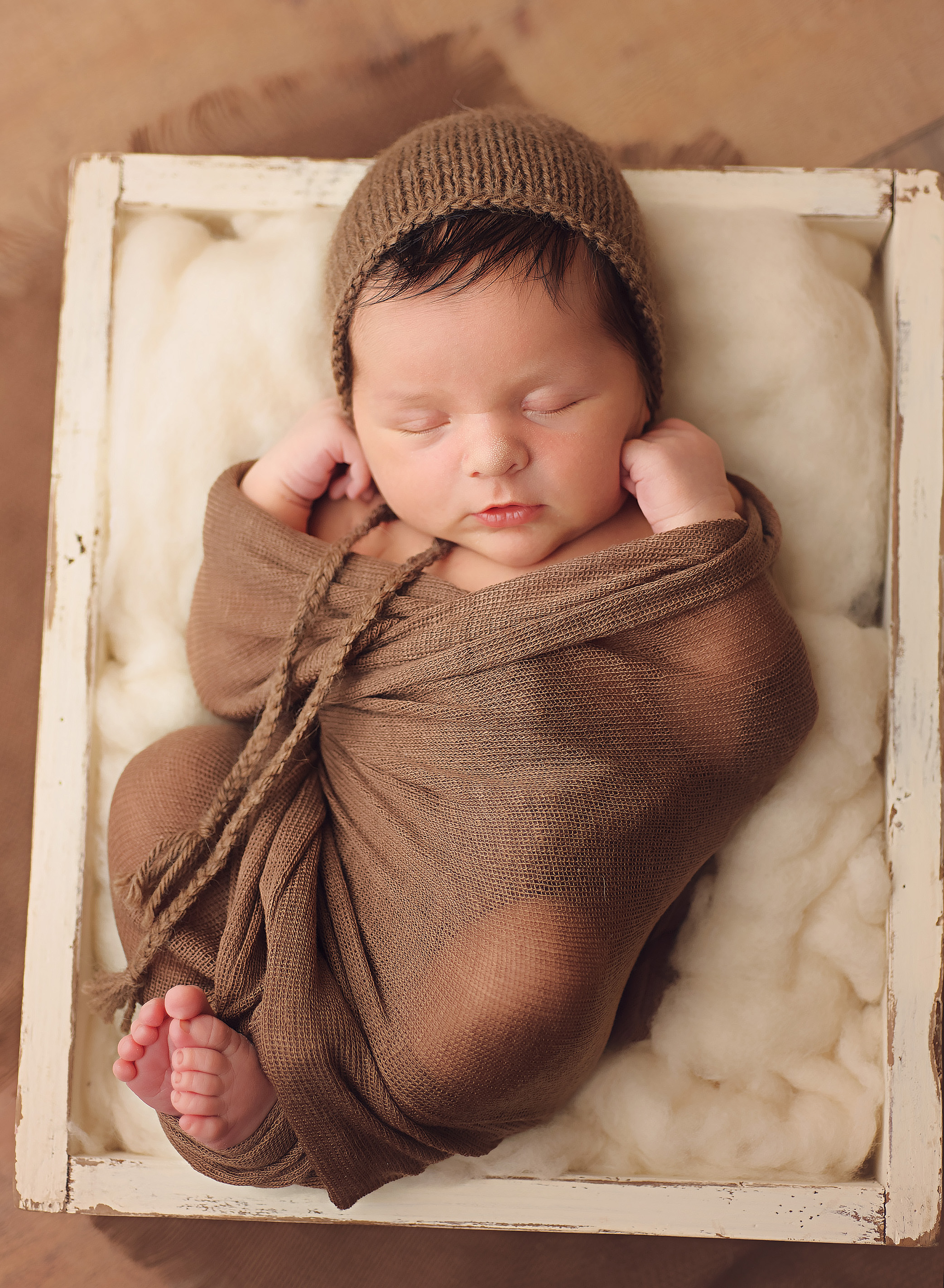 baby boy in brown wrap with brown hat