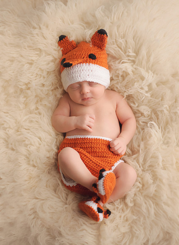baby in fox outfit on white fur