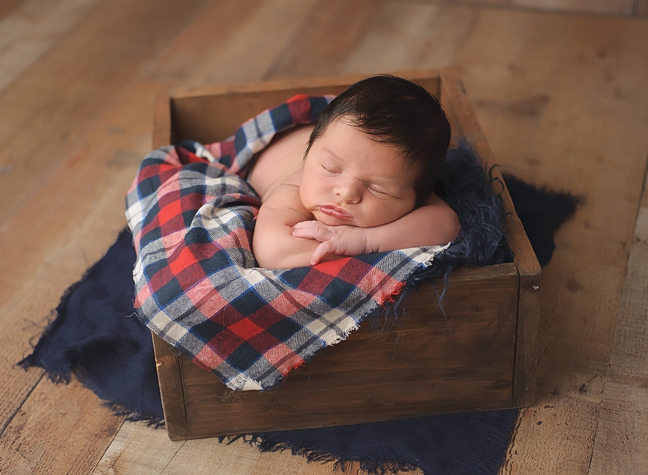 baby boy in wood box with plaid wrap