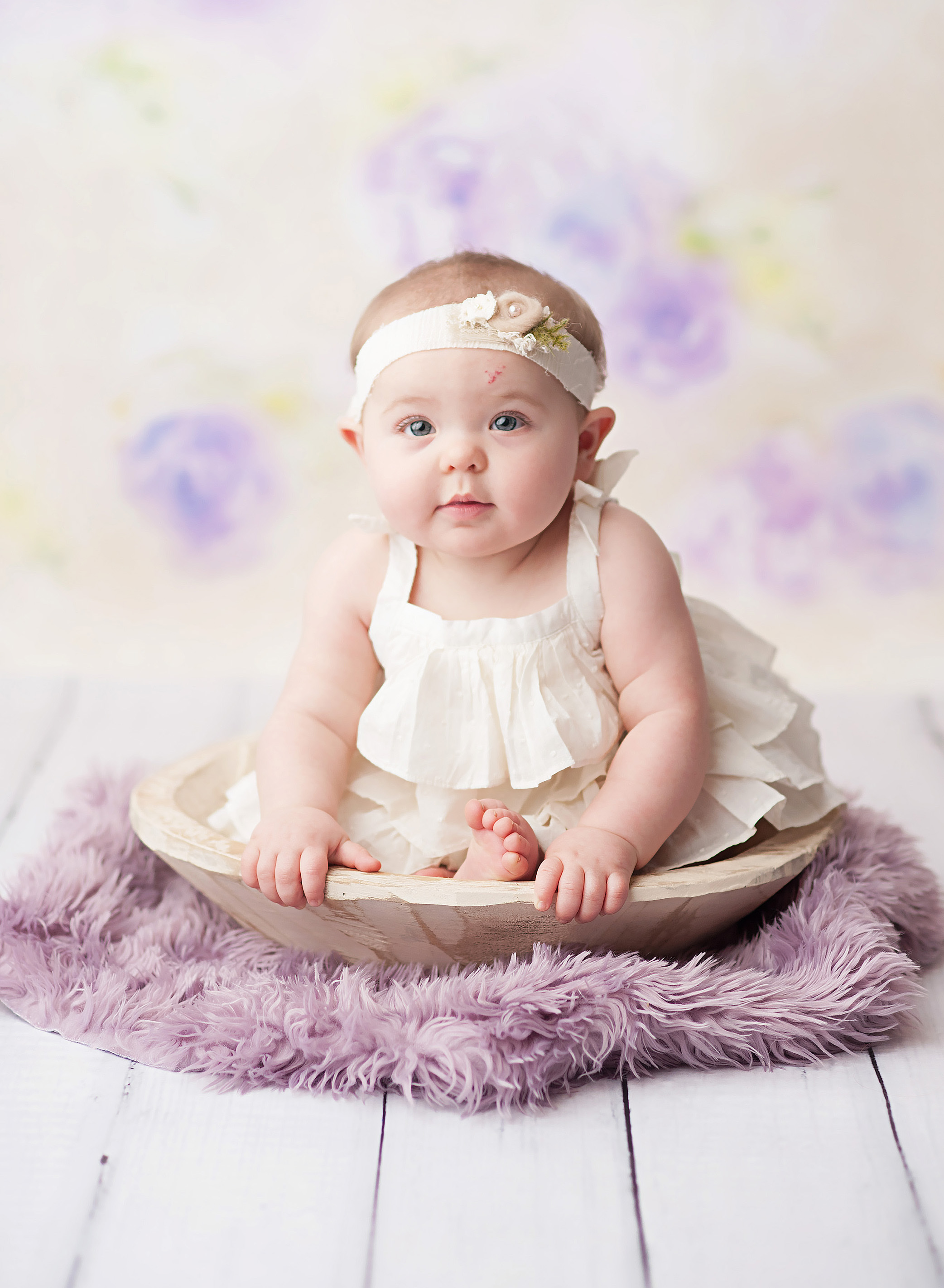 6 month old girl against purple floral bacdrop