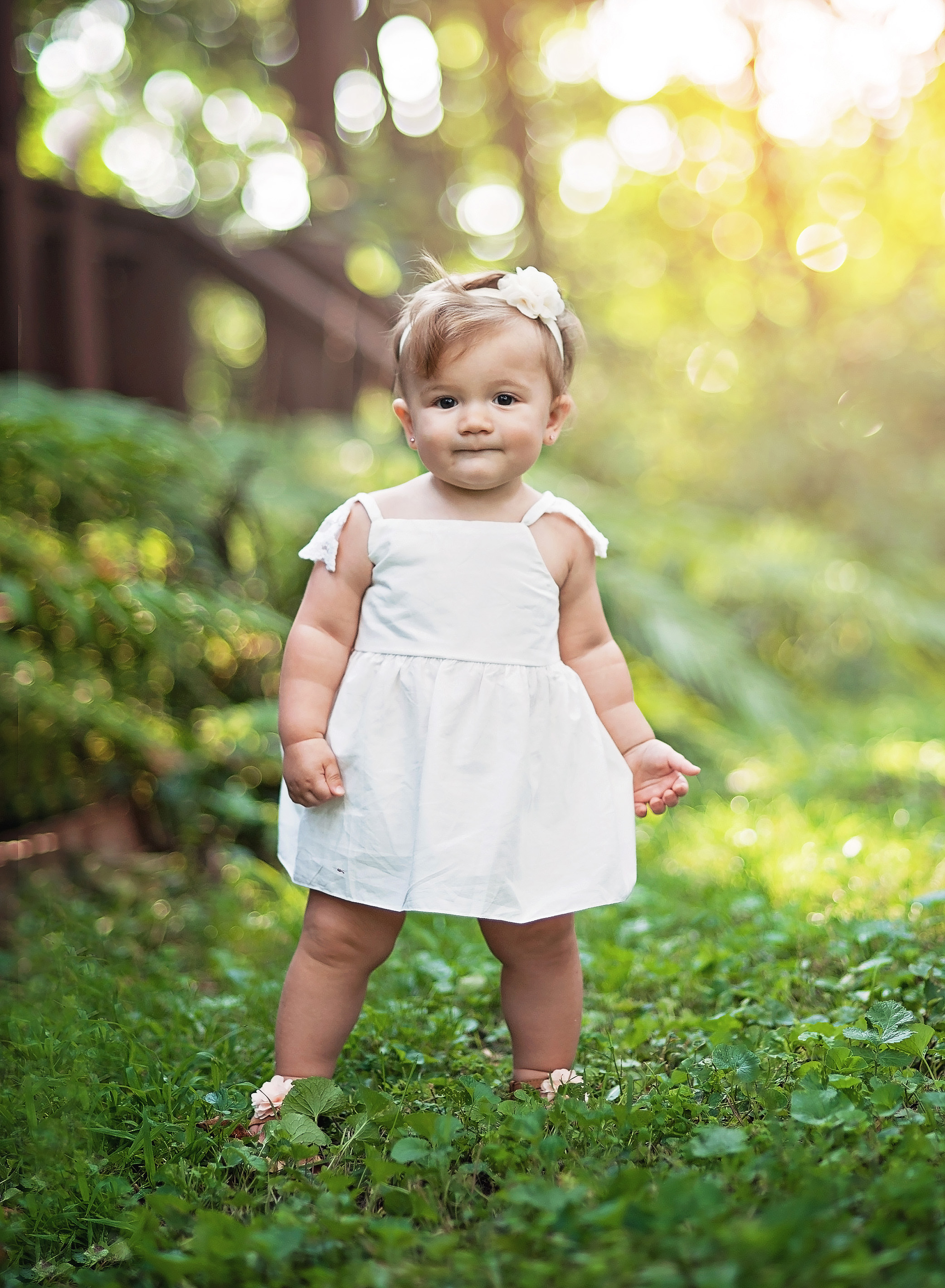baby girl in woods with white dress