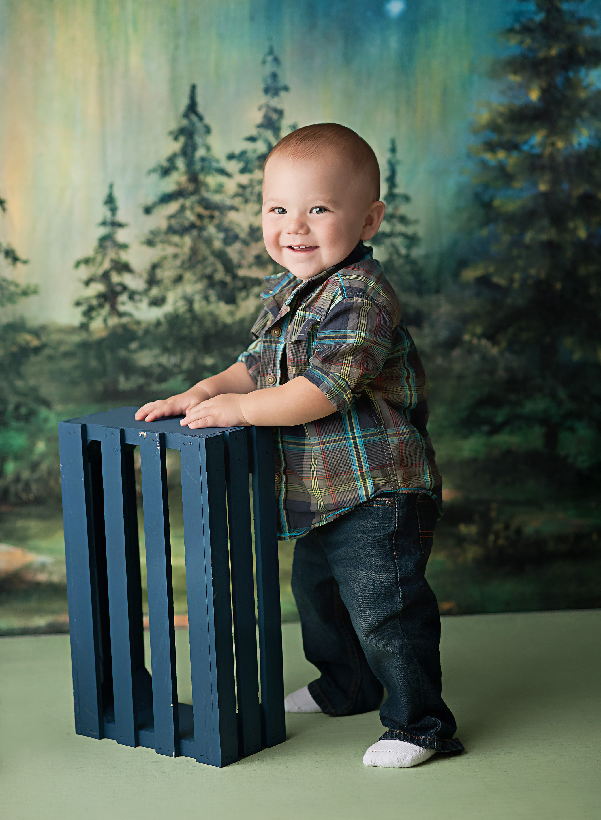 baby boy in plaid against woods backdrop