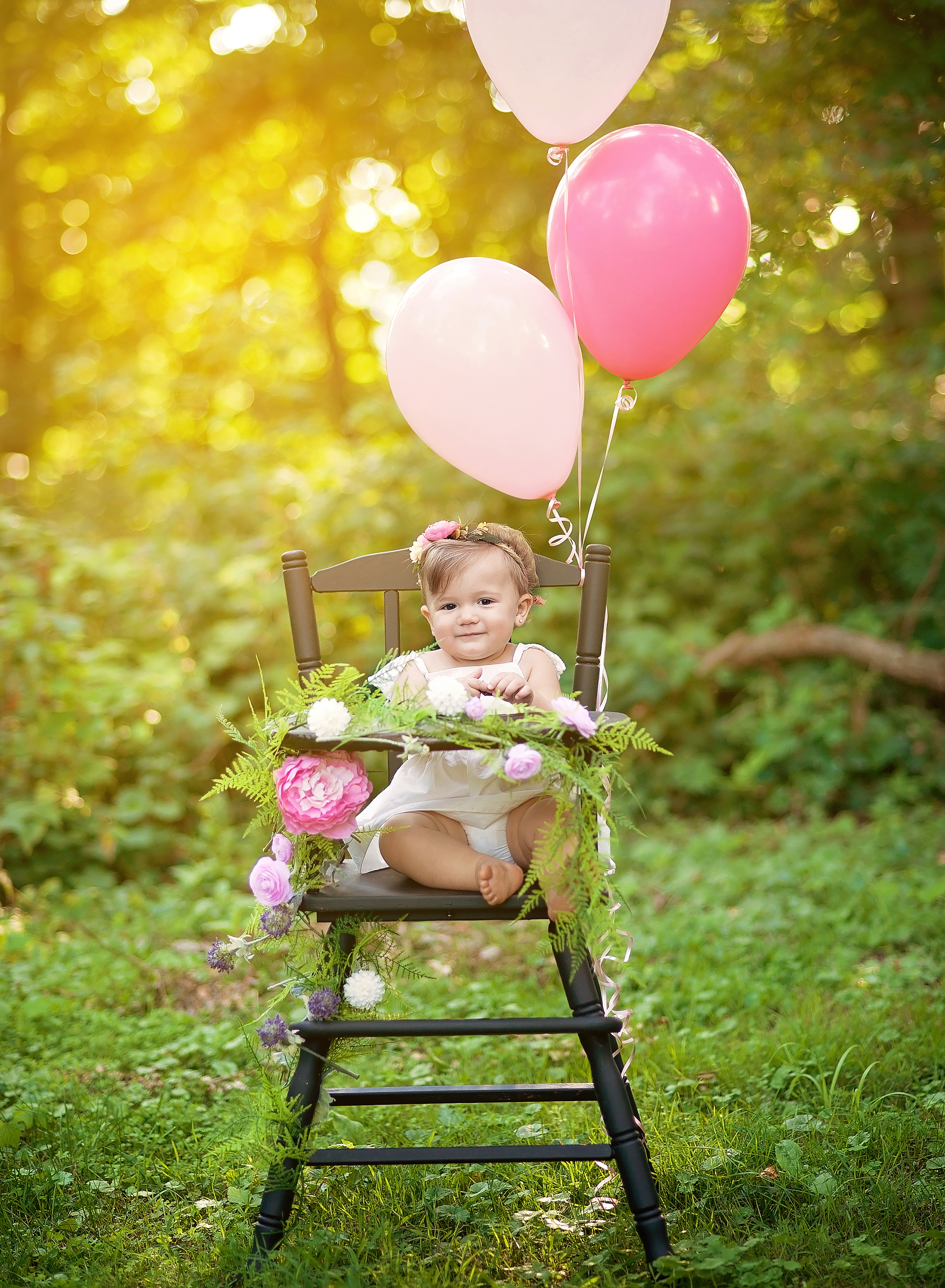 baby girl in black high chair with pink balloons