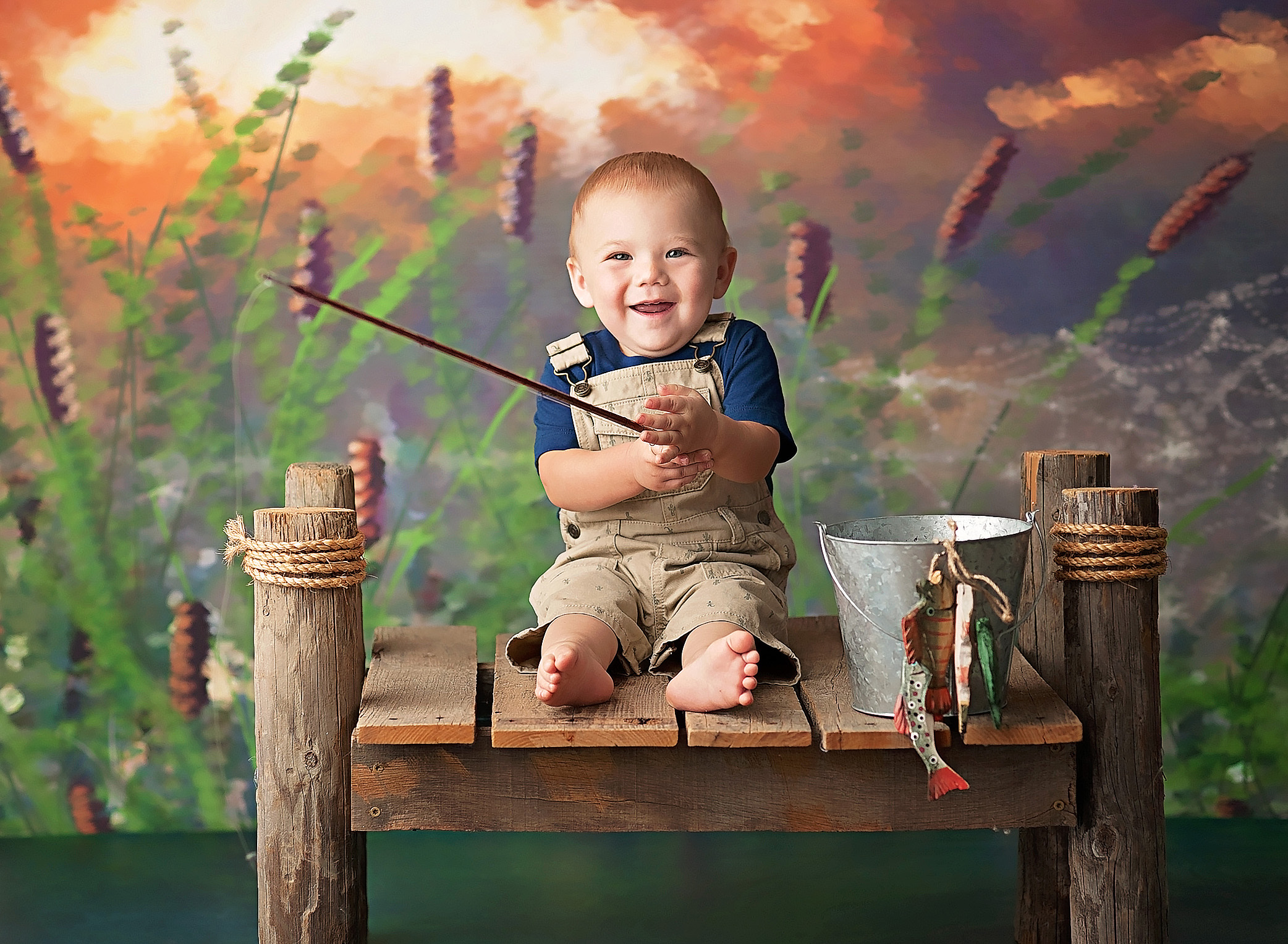 baby boy in overalls with fishing pole
