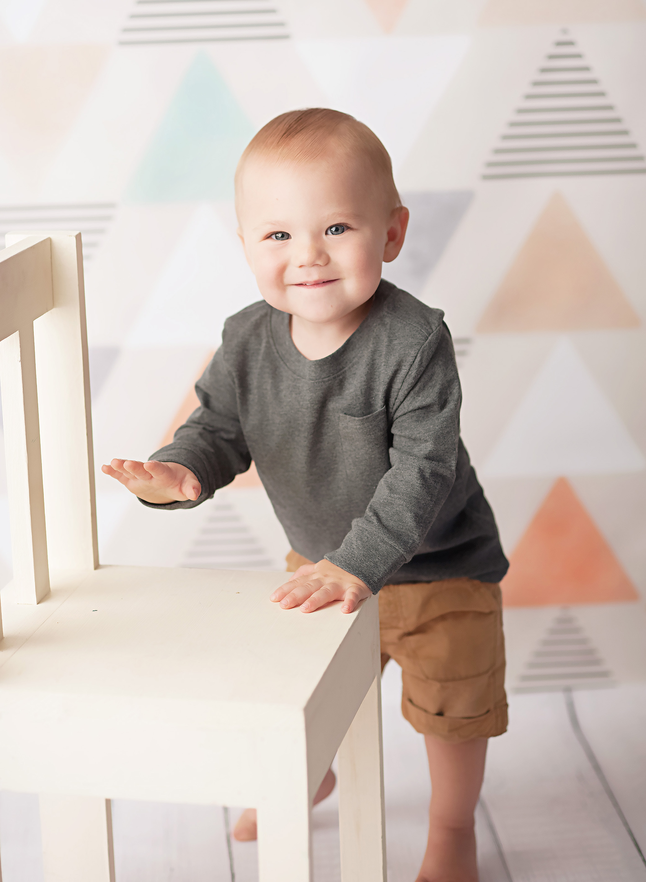 baby in grey standing by white chair