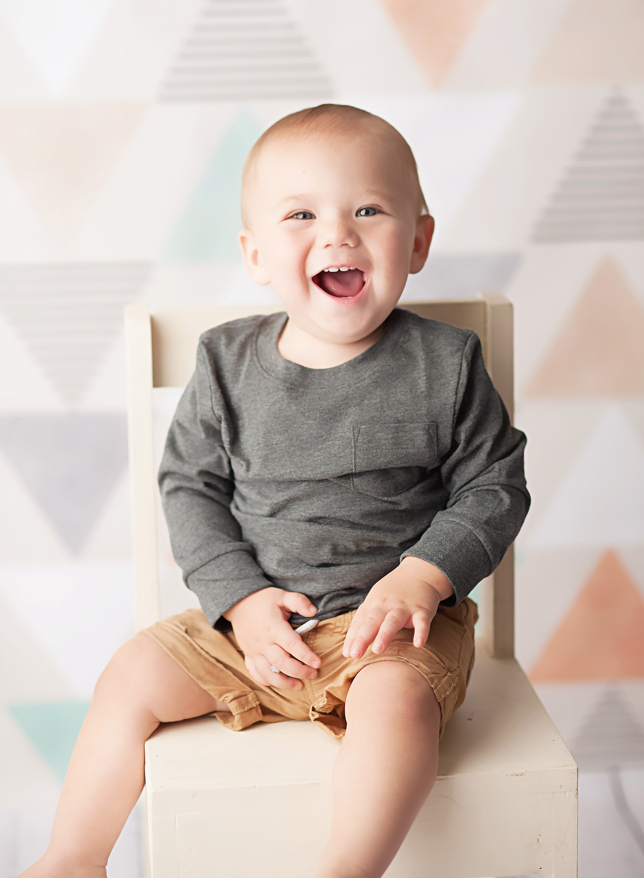 baby in grey sitting on white chair