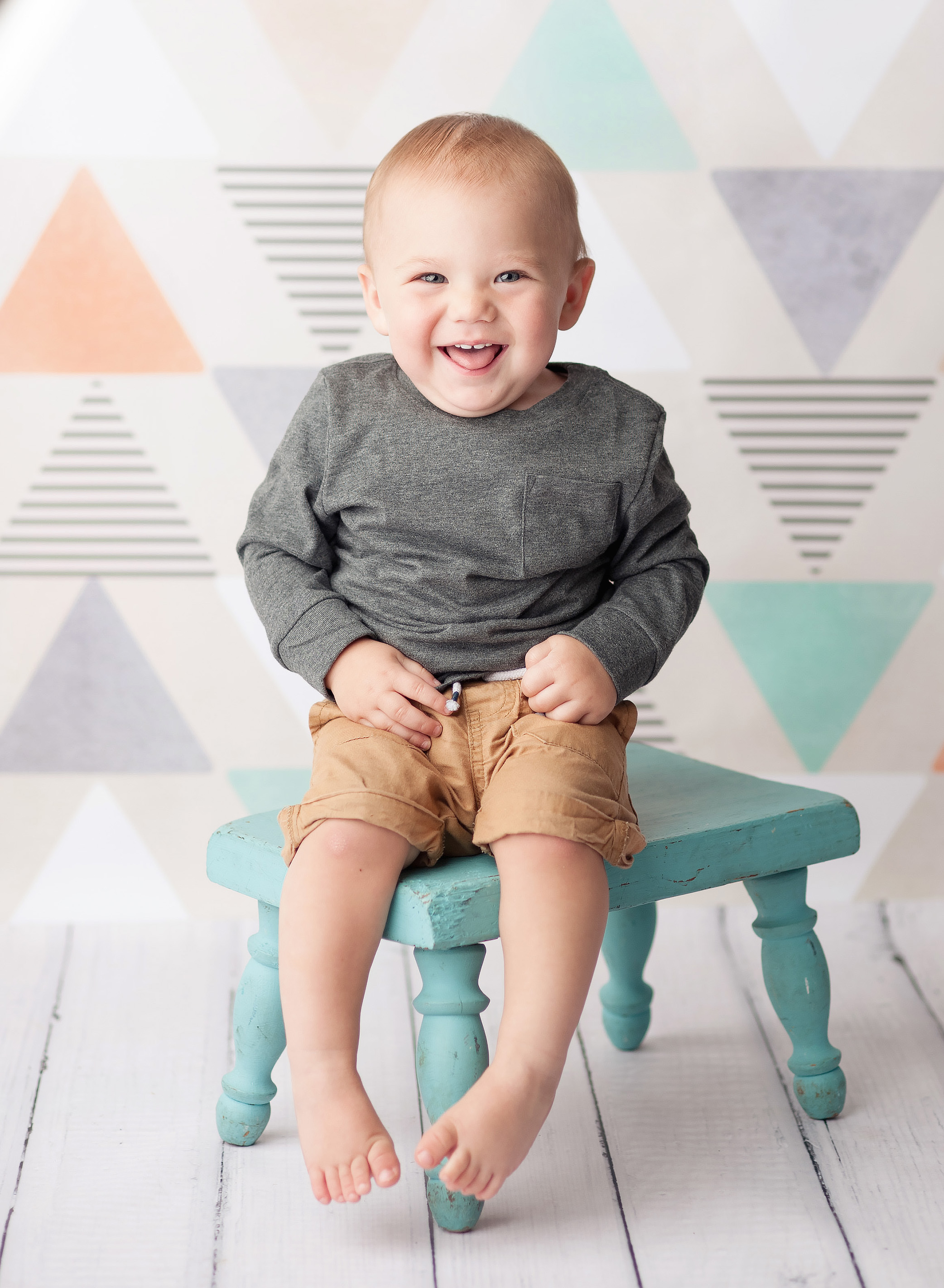 baby in grey sitting on blue stool