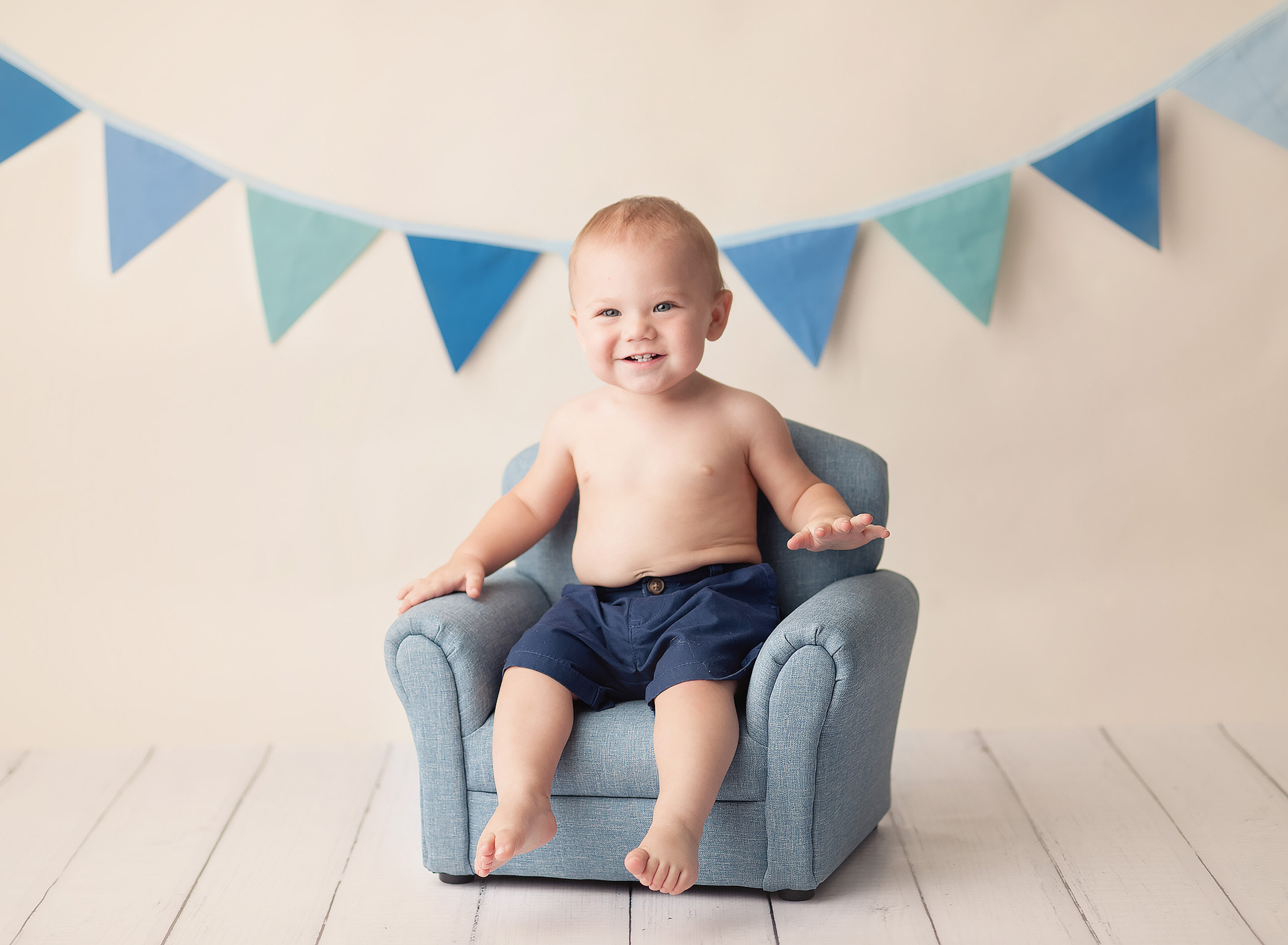 baby sitting on blue chair under flag banner