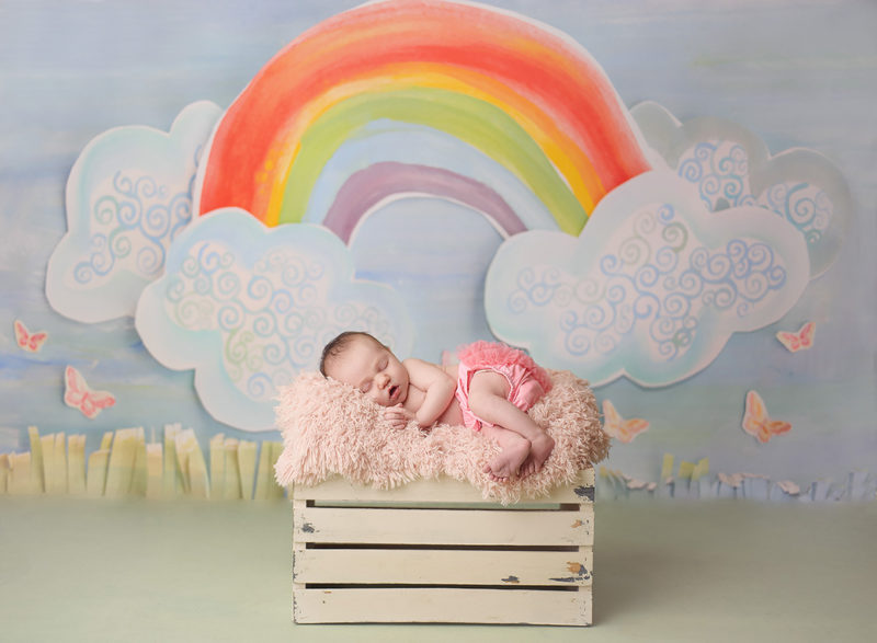 baby laying under a rainbow