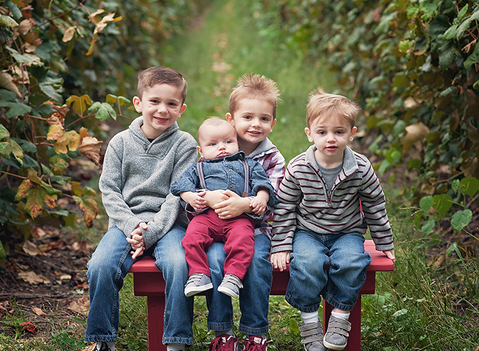 4 brother sitting on a red bench in grape vineyard