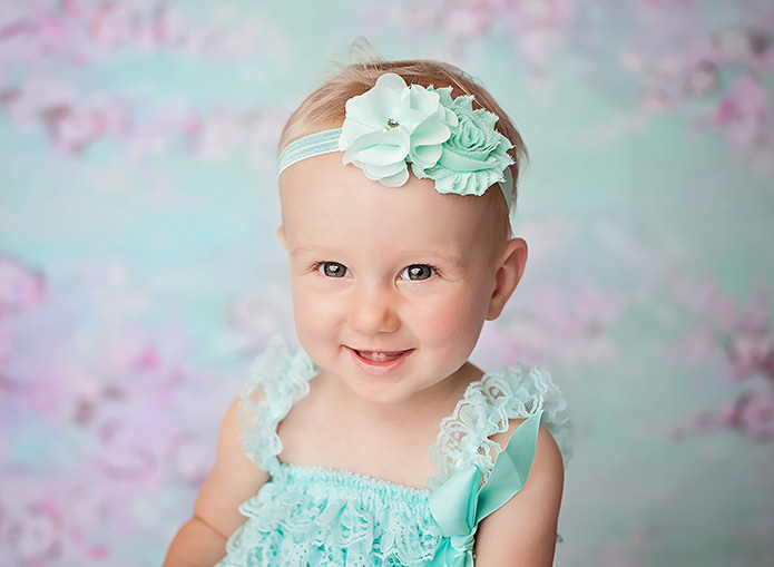 one year old girl with blue outfit and headband