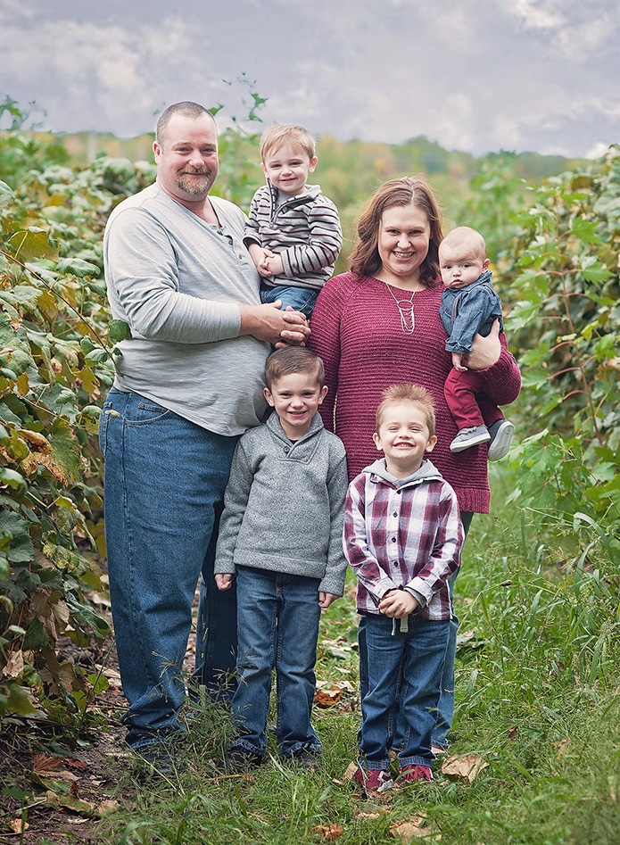 family standng in grape vineyard