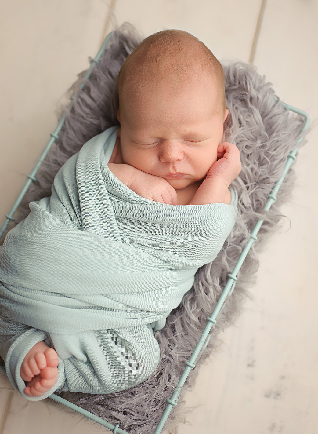 baby laying on grey fur and mint wrap