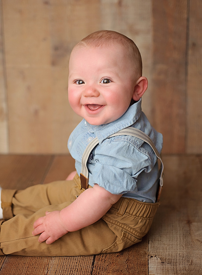 6 month old in suspenders against wooden wall