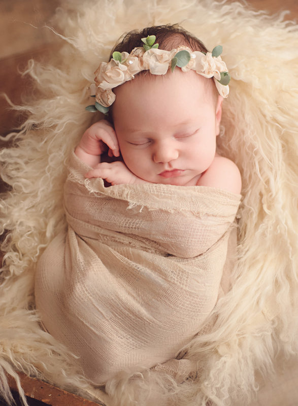 baby wrapped in neautral fabric with cream floral crown