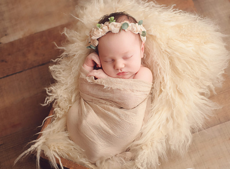 baby laying on white fur with cream floral crown