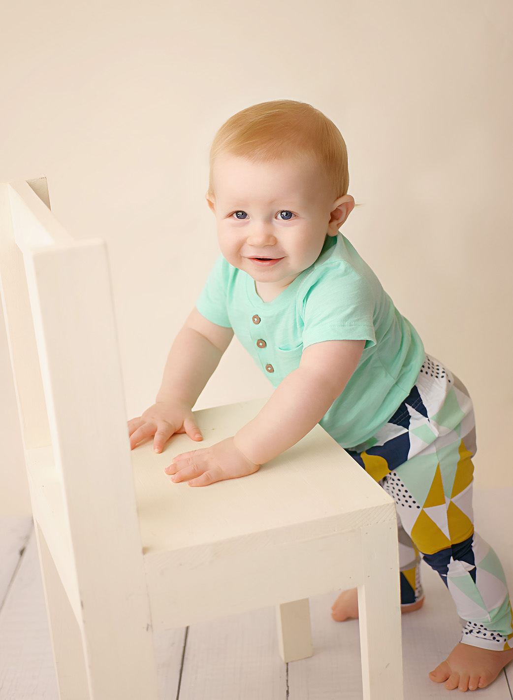 baby boy in mint shirt sitting on crate