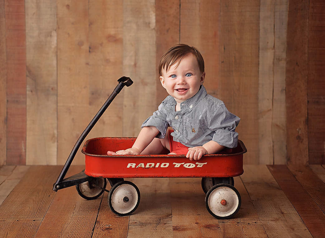 6 month old boy sitting in wagon with blue shirt on