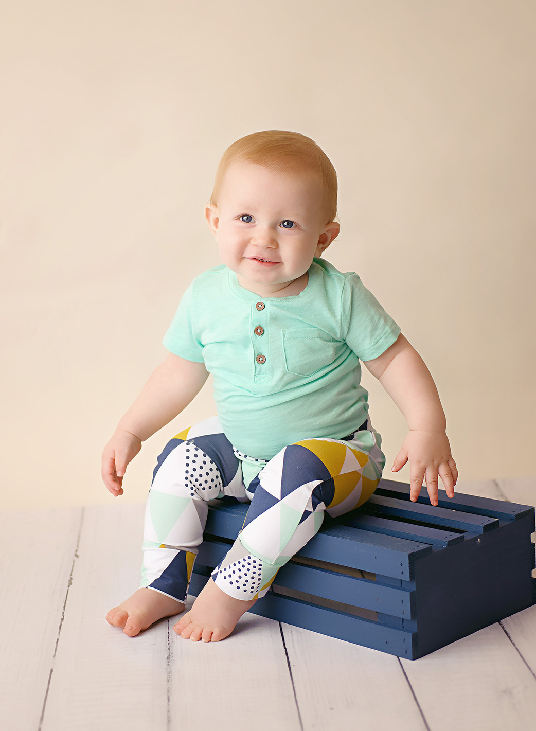 baby boy in mint shirt sitting on blue crate