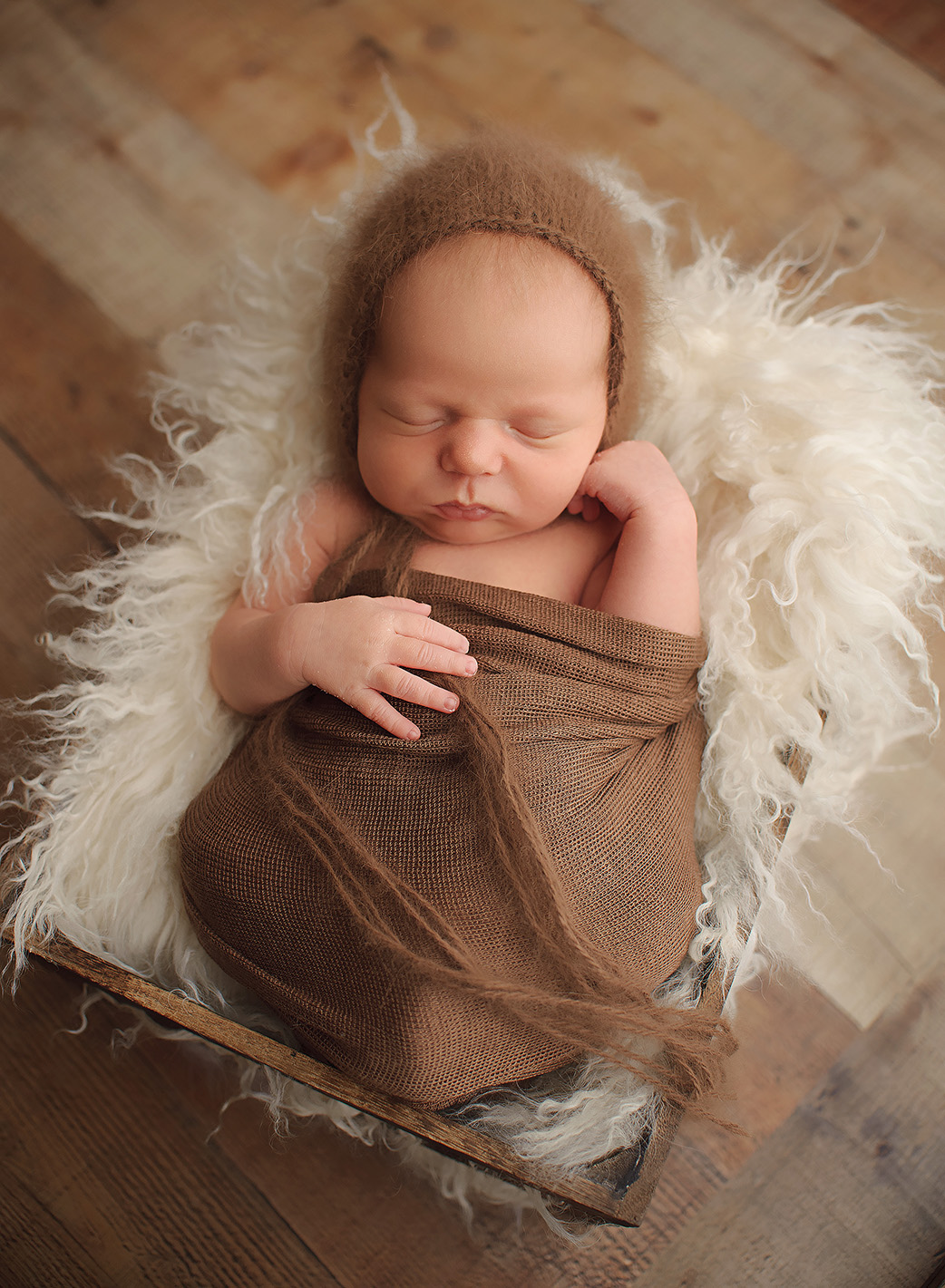 baby laying in white fur in brown wrap
