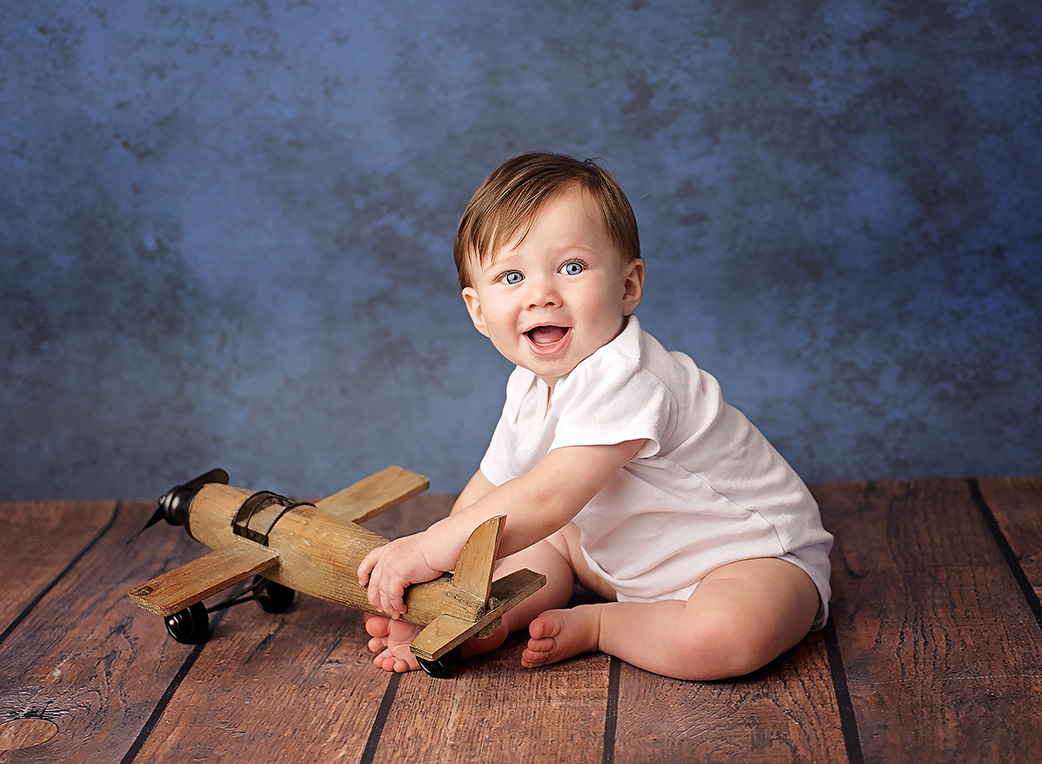 6 month old boy playing with wooden airplane