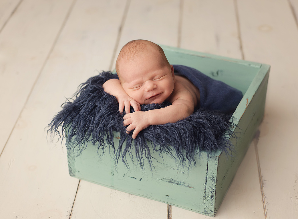 baby laying on navy blue fur
