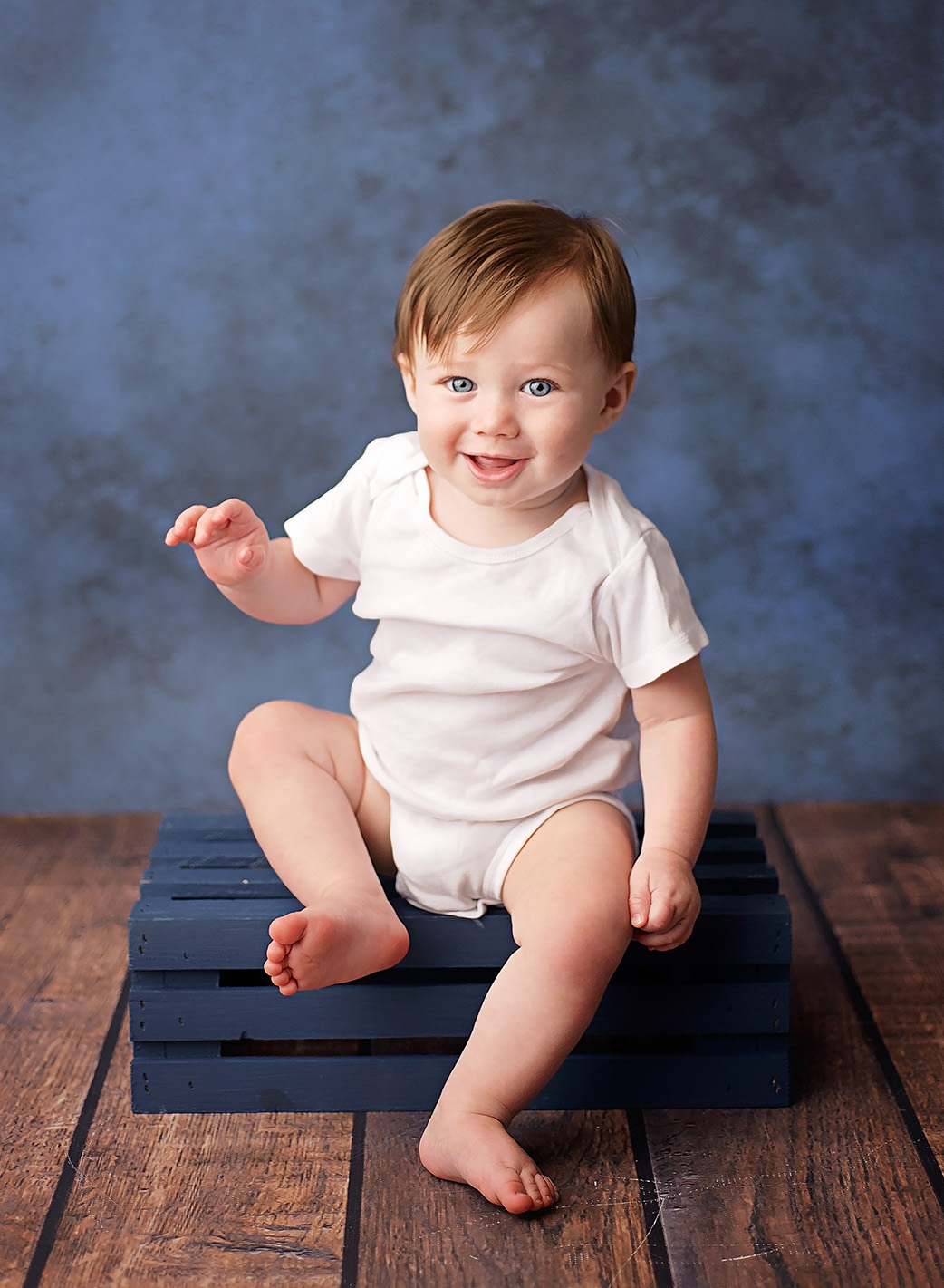 6 month old boy sitting on blue wooden crate