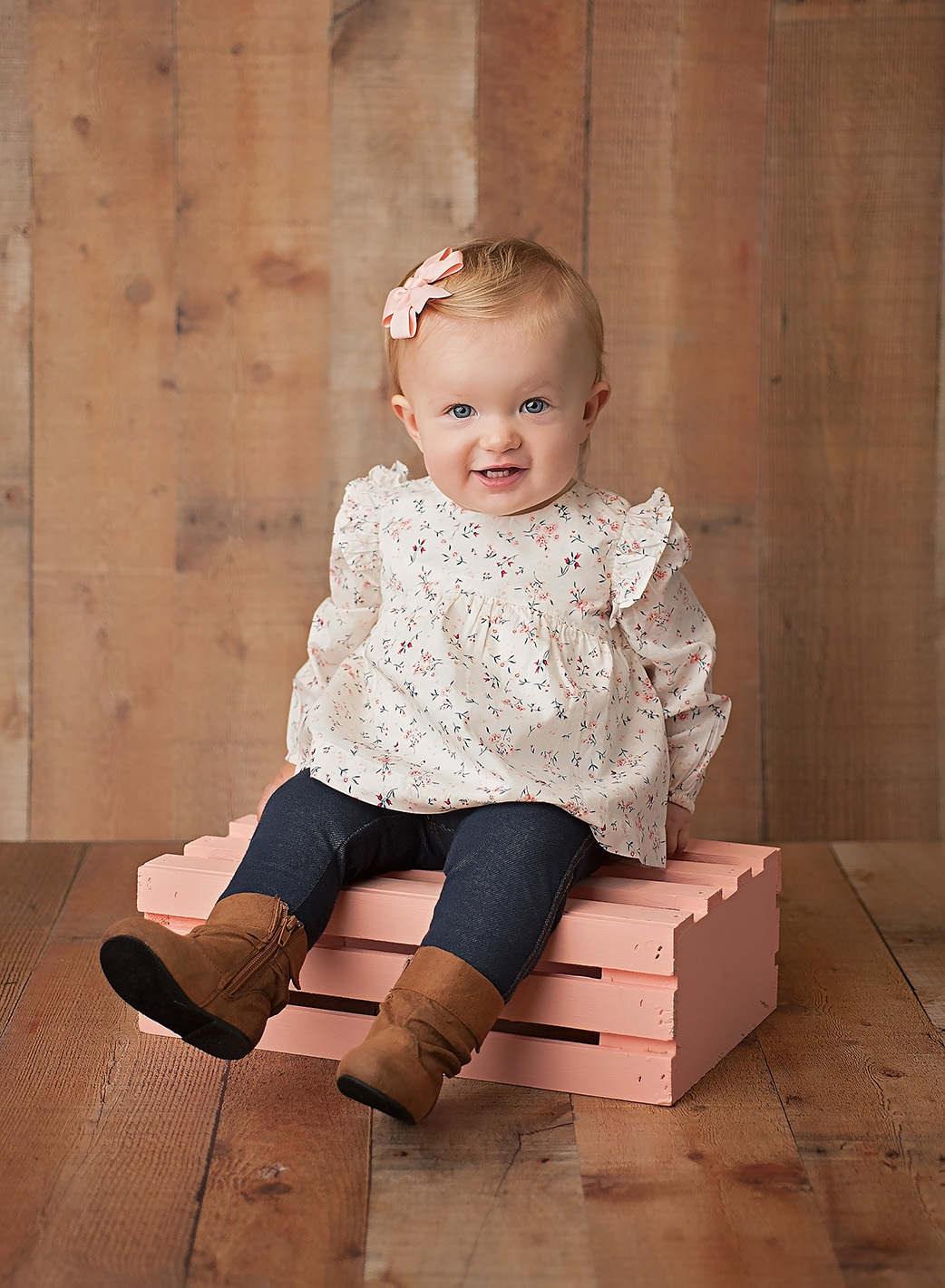 one year old baby girl on pink crate