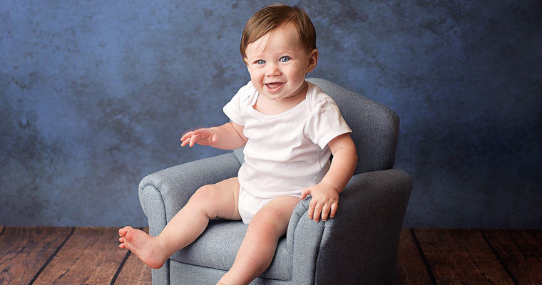 6 month old boy sitting in blue chair