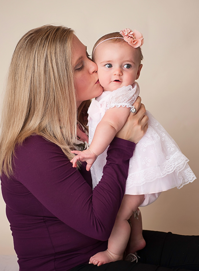 baby girl getting a kiss on the cheek from her mom