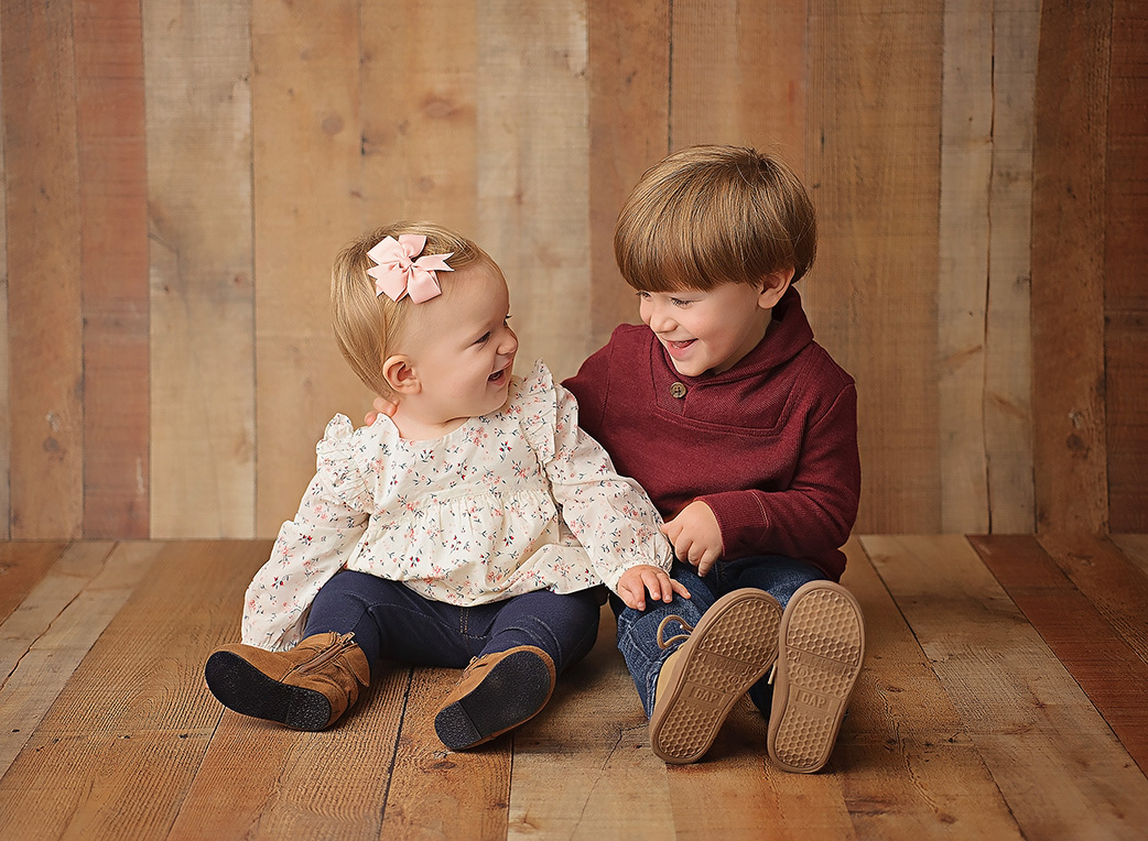 brother and sister on wooden backdrop